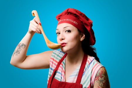 beautiful tattooed pinup cook girl on blue background photo