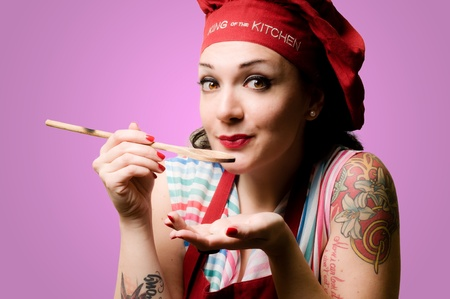 beautiful tattooed pinup cook girl on pink background photo