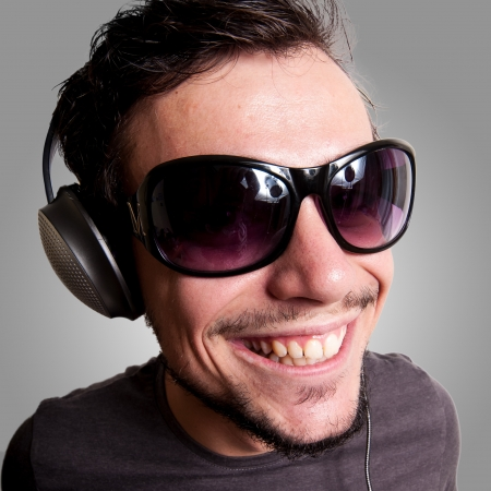 smiling guy with headphones and sunglasses on grey background photo