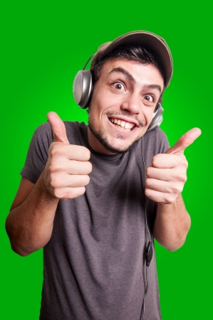 funny guy listening to music on green background photo