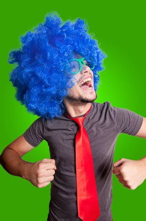 funny dancing guy with blue wig green eyeglasses and red tie on grey background photo