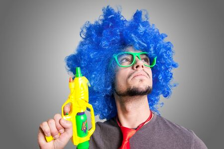 Funny guy with blue wig and water gun on grey background photo