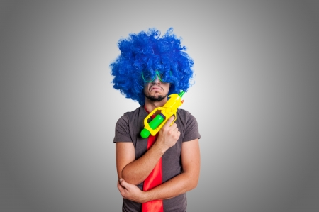 Funny guy with blue wig and water gun on grey background