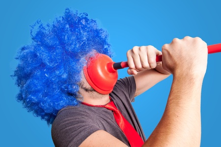 funny guy holding red plunger in his face with blue background
