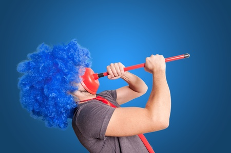 stifle: funny guy holding red plunger in his face with blue background