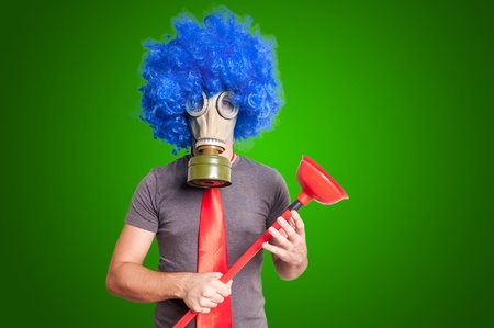 stifle: funny guy with gas mak, blue wig and red plunger on green background
