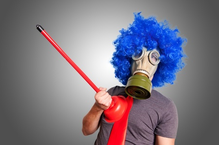 funny guy with gas mak, blue wig and red plunger on grey background photo