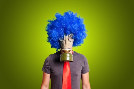 man with blue wig and gas mask on yellow background photo