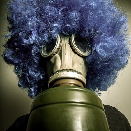 man with blue wig and gas mask on grey background photo