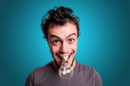 crazy guy with bulb in his mouth on blue background photo