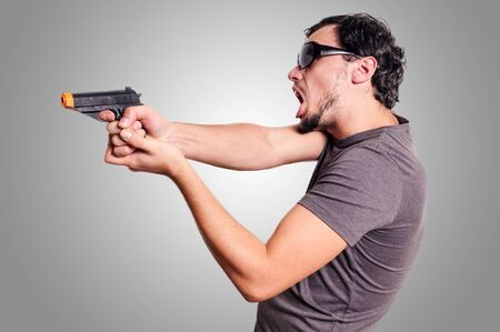 bad guy with gun on grey background Stock Photo - 16549634