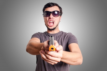 bad guy with gun on grey background photo