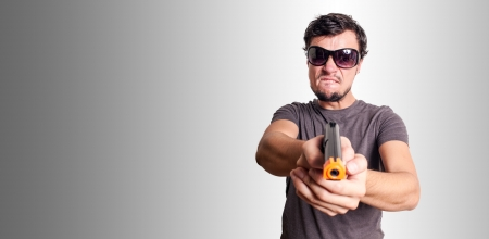 bad guy with gun on grey background photo
