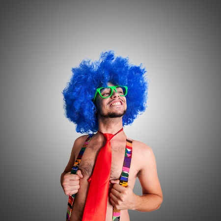loony: Funny guy shirtless with blue wig and red tie on grey background