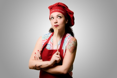beautiful tattooed pinup cook girl on grey background photo