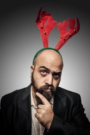 hombre con barba: duda navidad barba con expresiones divertidas sobre fondo gris Foto de archivo