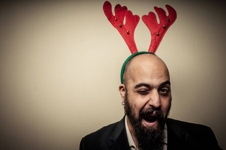 winking christmas bearded man with funny expressions on grey background photo