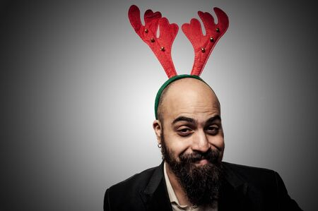 smiling christmas bearded man with funny expressions on grey background photo