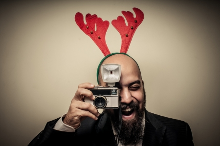 new year party: christmas bearded man holding old camera on grey background