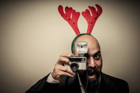 christmas bearded man holding old camera on grey background photo