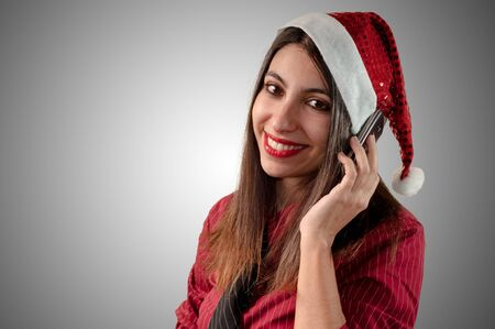 smiling business christmas girl at the phone on grey background photo