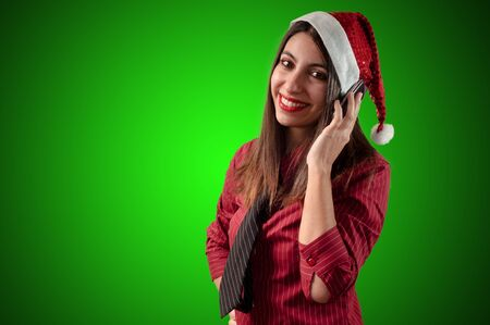 smiling business christmas girl at the phone on green background photo