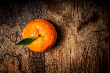 mandarin with leaf on brown wood Stock Photo - 16992643