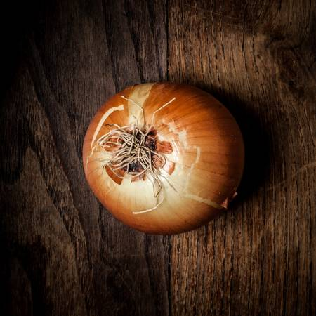 onion on textured brown wood photo
