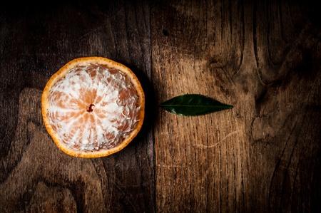 peeled mandarin with leaf on brown wood Stock Photo - 16992620