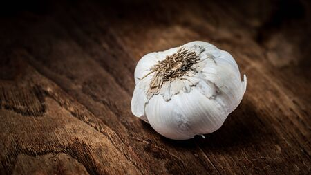 garlic on brown textured wood photo
