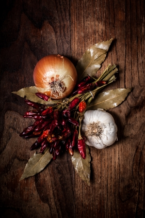 composition of chilies, onion and garlic on wood photo