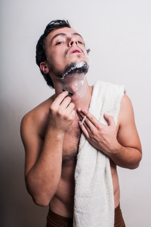 sexy man who shaves his beard on grey background photo