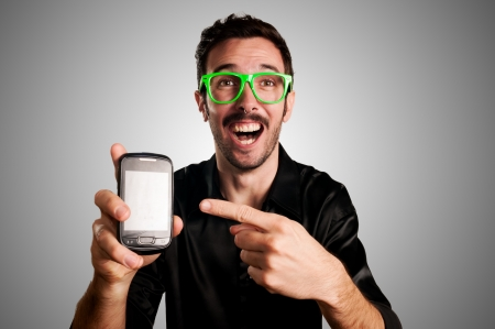 happy man showing phone on gray background photo