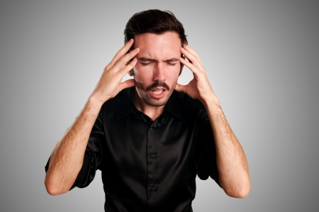 man with headache on gray background Stock Photo - 17369340