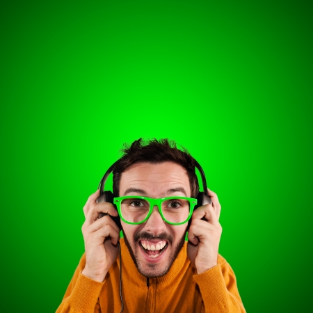 guy with headphones listening to music on green background photo