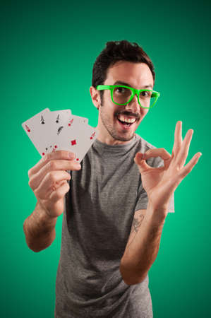 winner guy holding poker cards on green background photo