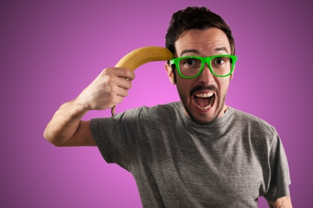 attempting: man attempting suicide with a banana on pink background
