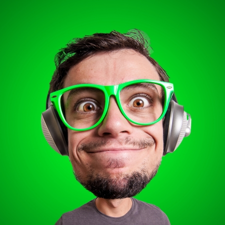 puppet man listening to music with big head on green background photo