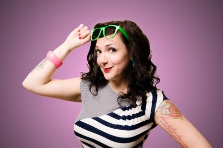 tattoed: chica pinup tatuado en el fondo rosado Foto de archivo