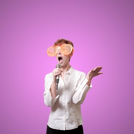 funny business woman singing with big orange eyeglasses on pink background photo