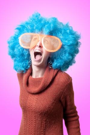 loco: chica divertida con peluca azul y grandes gafas naranjas sobre fondo rosa