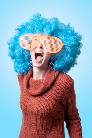 funny girl with blue wig and big blue eyeglasses on pink background Stock Photo - 18299623
