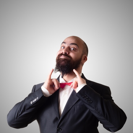 funny bearded elegant man with papillon on gray background photo