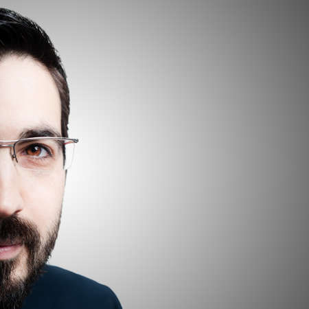 half face elegant bearded success business man on gray background photo