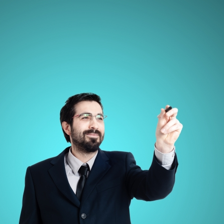 business man writing on imaginary screen on blue background photo