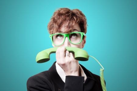 phone handset: donna d'affari con il telefono verde portatile come baffi su sfondo blu