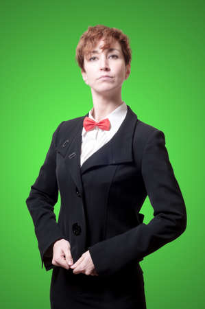 strutting: elegant businesswoman with bow tie on green background
