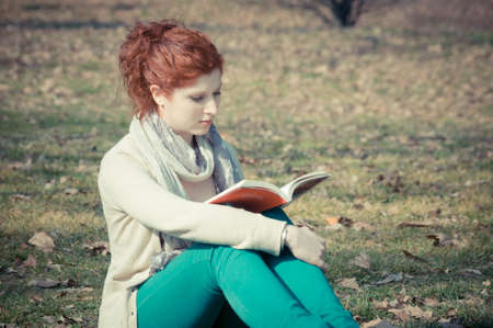 red long hair girl at the park reading in spring  photo