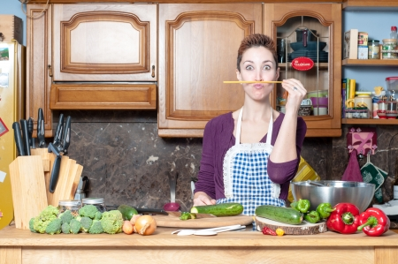 beautiful housewife cooking vegetables with spaghetti in the kitchen photo