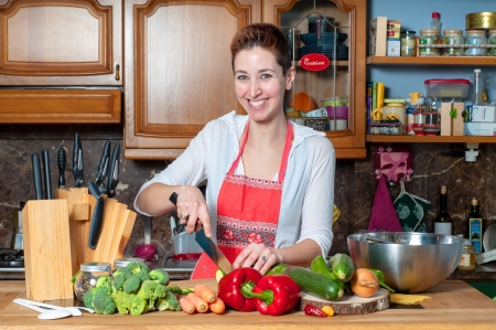 beautiful housewife cooking vegetables in the kitchen photo